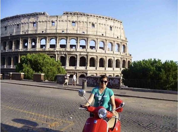 Student on scooter in front of the Colosseum in Rome
